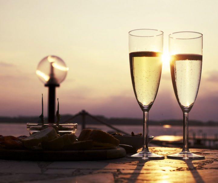 dîner romantique au coucher du soleil avec coupes de champagne