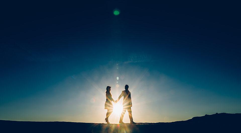 couple devant un coucher de soleil se tenant la main